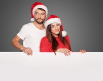 结合拿着一个空白的委员会的佩带的圣诞老人帽子 免版税库存照片