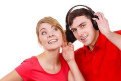 结合有耳机的两个朋友听到音乐的 免版税库存照片