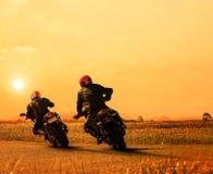 结合朋友骑自行车在沥青高速公路agains的摩托车车手 库存照片