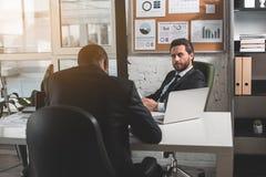 合格的商人在办公室工作 免版税库存照片