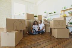 结合计划他们新的厨房选址在地板 移动向一个新的公寓和运载的箱子的年轻家庭 免版税库存图片