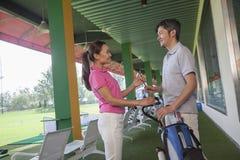 结合谈话和挥动在高尔夫球场,拿着高尔夫俱乐部 图库摄影