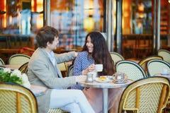 结合饮用的咖啡和在巴黎人咖啡馆的吃新月形面包 库存图片