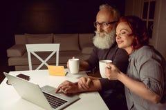 结合饮用的茶和在家使用膝上型计算机一起 免版税图库摄影
