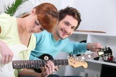 吉他他的实习教师 免版税图库摄影