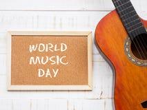 吉他和委员会与世界音乐天在白色木t发短信 库存图片