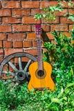 吉他和老马车车轮 免版税库存图片