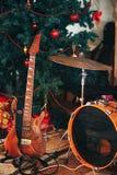 吉他和鼓在圣诞树下 免版税库存照片