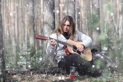 吉他弹奏者在野餐的森林 有音响的一位音乐家 库存照片