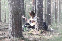 吉他弹奏者在野餐的森林 有音响的一位音乐家 免版税库存图片