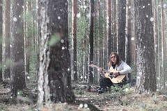 吉他弹奏者在野餐的森林 有音响的一位音乐家 免版税库存照片