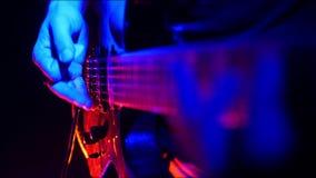 吉他弹奏者声调和开始使用在他的在明亮的霓虹照明设备的吉他 股票录像