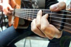 吉他弹奏者弹古典吉他,特写镜头 软绵绵地集中 免版税库存照片