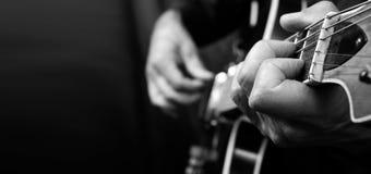 吉他弹奏者手和吉他接近  电吉他使用 复制空间 黑色白色 库存图片