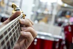 吉他弹奏者` s手,特写镜头和软的焦点,采取在吉他fretboard的akrod,以鼓集合为背景 库存图片