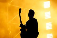 吉他演奏员,吉他弹奏者剪影在音乐会阶段执行 免版税库存图片