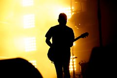 吉他演奏员,吉他弹奏者剪影在音乐会阶段执行 免版税库存照片