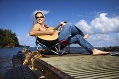 吉他演奏坐的年轻人的湖边人 免版税库存图片