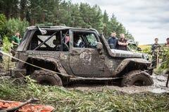 吉普的参加者通过一个深泥泞的坑 免版税库存照片
