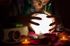 吉普赛算命者妇女用她的在水晶球上的手 库存照片