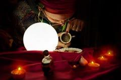 吉普赛观察敏锐的妇女读从空的咖啡杯的时运 库存图片