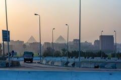 吉萨棉,埃及2010年2月:有金字塔的城市街道在背景中 库存图片