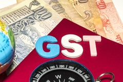 吉隆坡,马来西亚12月2,2017 :GST词特写镜头与地球、指南针和卢比笔记的 选择聚焦和庄稼fragme 免版税图库摄影