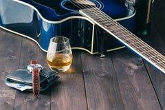 吉他、金钱和威士忌酒在木桌上 免版税图库摄影