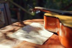 吉他和比分在桌上在庭院里 免版税图库摄影