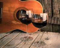 吉他和酒在一顿木桌浪漫晚餐 库存照片