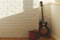 吉他在砖屋子里 免版税库存照片