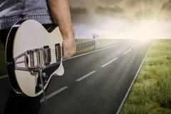吉他弹奏者和他的吉他在路 库存照片