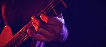 吉他弹奏者执行的中央部位 库存照片