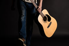 吉他弹奏者来与在他的左手的一把声学吉他,在黑背景 免版税库存照片