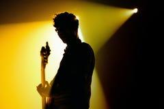 吉他弹奏者的剪影我们是标准的(带)执行在迪斯科舞厅活力 库存图片