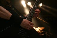 吉他弹奏者的手 免版税库存照片