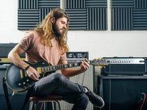 吉他弹奏者记录轨道在演播室 免版税库存照片