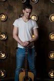 吉他弹奏者,音乐 一个年轻人在背景中站立与一把声学吉他与在他后的光 垂直的框架 免版税库存图片