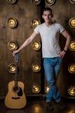 吉他弹奏者,音乐 一个年轻人在背景中站立与一把声学吉他与在他后的光 垂直的框架 库存照片