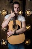 吉他弹奏者,音乐 一个年轻人在背景中站立与一把声学吉他与在他后的光 垂直的框架 免版税图库摄影