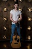 吉他弹奏者,音乐 一个年轻人在背景中站立与一把声学吉他与在他后的光 垂直的框架 图库摄影