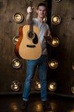 吉他弹奏者,音乐 一个年轻人在他的手上站立与一把声学吉他,在与光的背景中在他后 垂直 库存照片