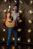 吉他弹奏者,音乐 一个年轻人在他的手上站立与一把声学吉他,在与光的背景中在他后 垂直 库存图片