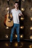 吉他弹奏者,音乐 一个年轻人在他的手上站立与一把声学吉他,在与光的背景中在他后 垂直 免版税库存图片