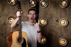 吉他弹奏者,音乐 一个年轻人在他的手上站立与一把声学吉他,在与光的背景中在他后 horizonta 免版税库存照片