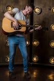 吉他弹奏者,音乐 一个年轻人弹在背景的一把声学吉他与在他后的光 垂直的框架 免版税图库摄影