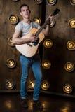 吉他弹奏者,音乐 一个年轻人弹在背景的一把声学吉他与在他后的光 垂直的框架 免版税库存照片