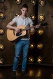 吉他弹奏者,音乐 一个年轻人弹在背景的一把声学吉他与在他后的光 垂直的框架 库存图片