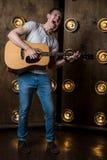 吉他弹奏者,音乐 一个年轻人弹在背景的一把声学吉他与在他后的光 垂直的框架 图库摄影