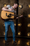 吉他弹奏者,音乐 一个年轻人弹在背景的一把声学吉他与在他后的光 垂直的框架 库存照片